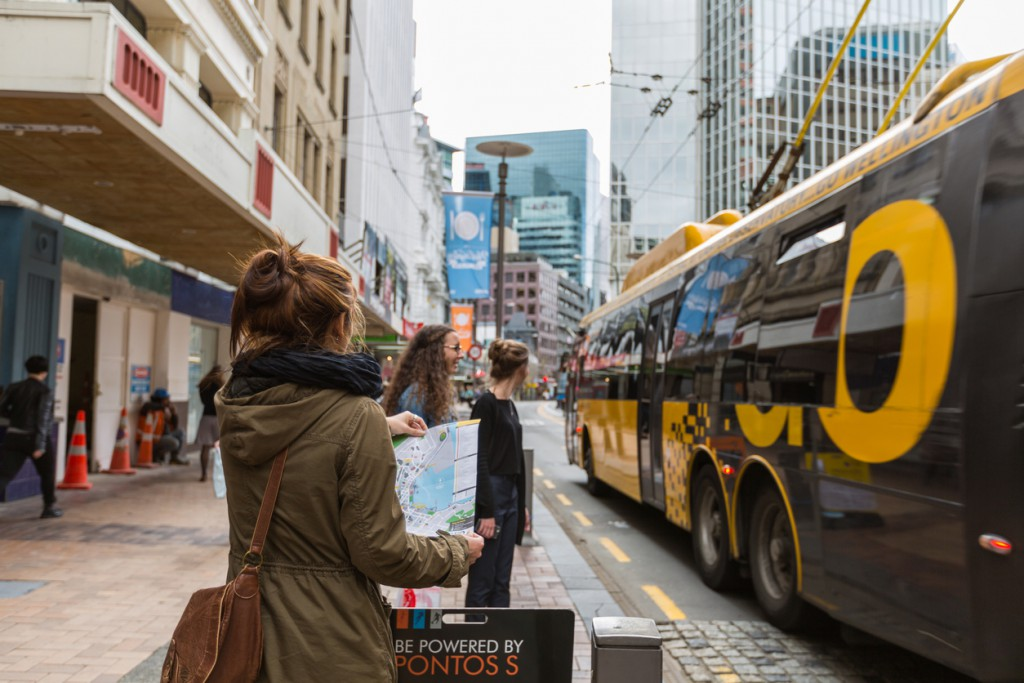 Wellington, New Zealand - September 3, 2014: New Zealand - Unidentified asian woman tourist look at the map to check the bus route while waiting for the bus on in Wellington, New Zealand. Wellington is the capital of New Zealand.